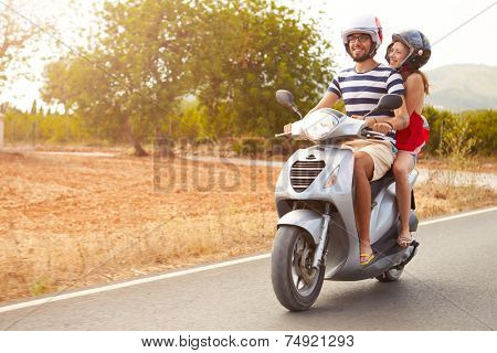 Young Couple Riding Motor Scooter Along Country Road