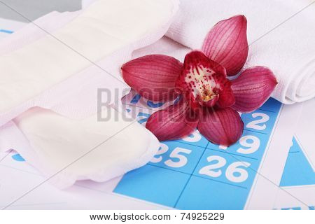 Sanitary pads and lilac orchid on blue calendar background