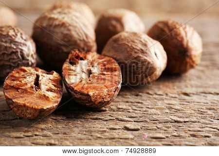 Nutmegs on wooden background