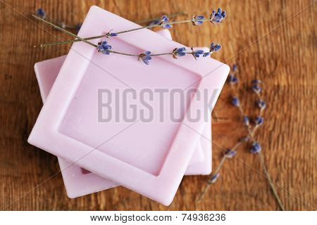 Bars of natural soap with dried lavender on wooden background