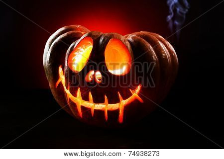 Halloween pumpkin on table on dark red background