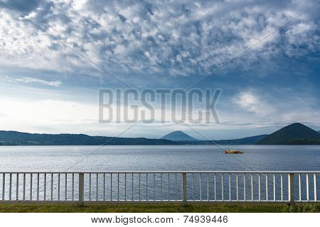 Cruising At Lake Toya With Mountain In Background, Hokkaido, Japan