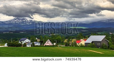 Houses In Grass Field With Mountain Ranges Background