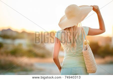 The girl in a summer hat with large fields.
