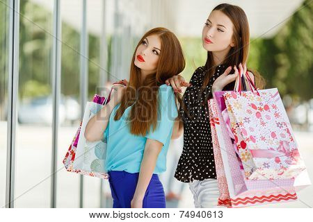 Two girlfriends with shopping bags.