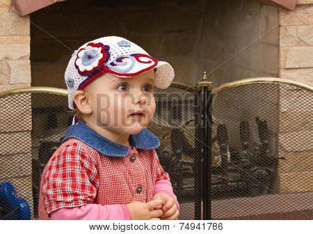 little girl by the fireplace