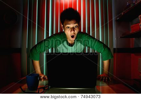 Young Teen with eyeglasses acting surprised in front of a laptop computer