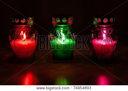 Colored Burning Votive Candles In The Dark