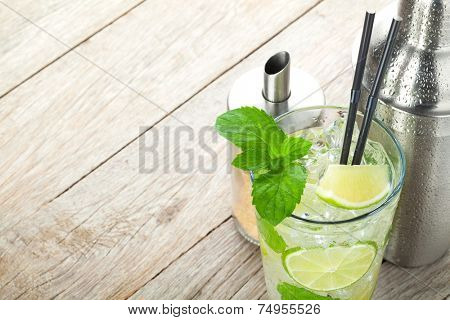 Fresh mojito cocktail and bar utensils on wooden table with copy space