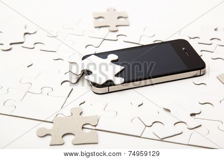 White puzzle with mobile phone on the table