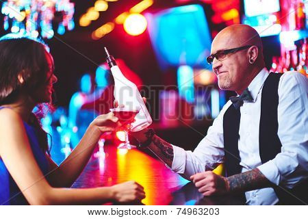 Bald male with bottle and young girl with martini chatting in the bar