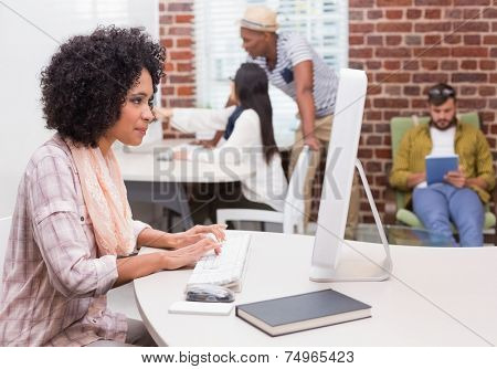 Concentrated casual young woman using computer in the office