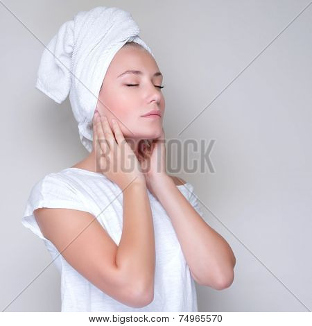 Portrait of cute female with closed eyes and towel on head touching face, studio shot, applying facial cream, pampering and health care concept