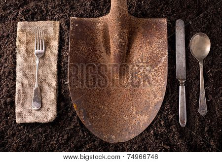 Rusted Shovel On Soil Background With Fork, Knife, Spoon, And Napkin.