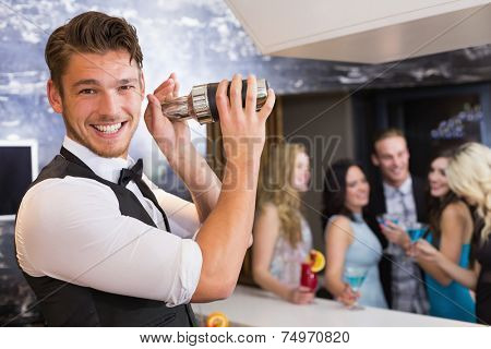Handsome barman smiling at camera making a cocktail at the bar