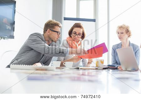 Creative businesspeople analyzing documents at desk in office