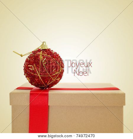 a gift with a red ribbon and a christmas ball, and the sentence joyeux noel, merry christmas in french, on a beige background, with a retro effect