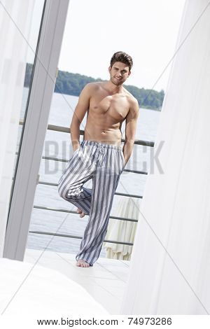 Full length portrait of muscular young man leaning on railing of hotel balcony