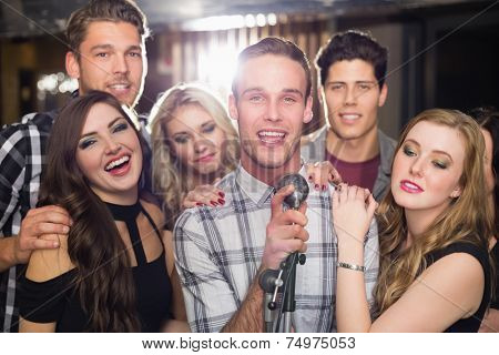 Happy friends singing karaoke together at the bar
