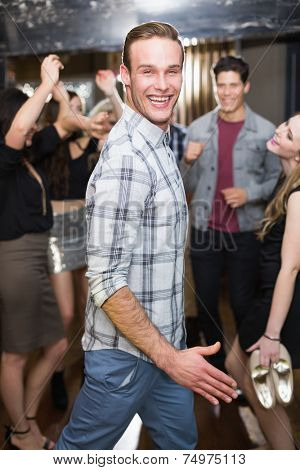 Stylish man smiling on the dancefloor at the bar