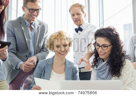 Happy businesspeople working on laptop in creative office