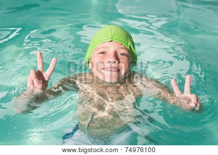 Cute kid swimming in the pool at the leisure center