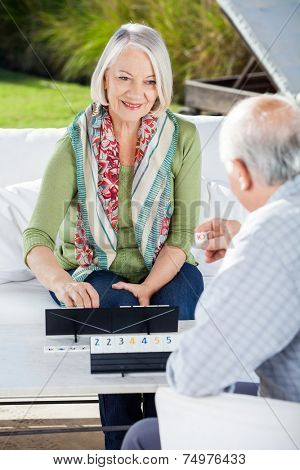 Happy senior woman playing rummy with man at nursing home porch