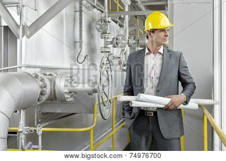 Young male architect holding rolled up blueprints by industrial machinery