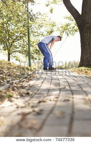 Full length of tired young man standing on path after running in park