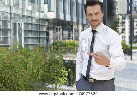 Portrait of angry businessman showing middle finger outside office building
