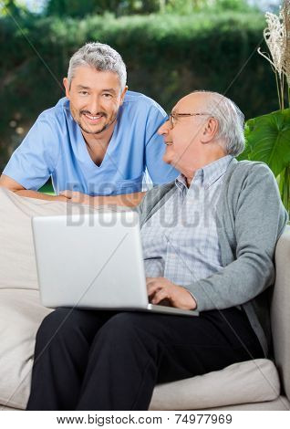 Portrait of male caretaker with senior man using laptop on couch at nursing home porch