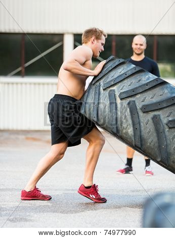 Side view of young sportsman flipping truck tire outdoors