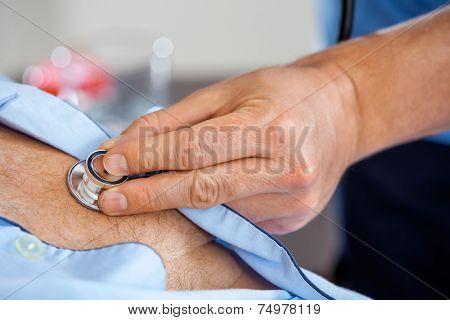 Closeup of male caretaker examining senior man with stethoscope at nursing home