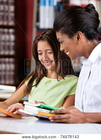 Happy female librarian and schoolgirl looking together at book in library