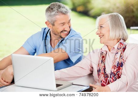 Happy senior woman and caretaker looking at each other while using laptop on nursing home porch