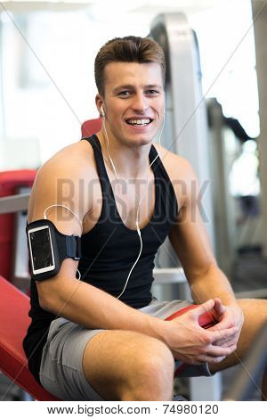 sport, bodybuilding, lifestyle, technology and people concept - smiling young man with smartphone and earphones in gym