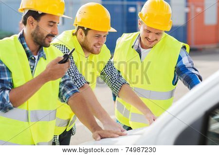 business, building, teamwork and people concept - group of smiling builders in hardhats with radio and car outdoors