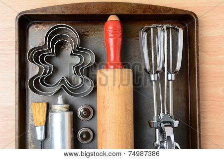 High angle closeup of the kitchen tools needed for making holiday cookies. The items are arranged on a well used metal baking sheet. Horizontal format with rolling pin, mixer, cookie cutters and press