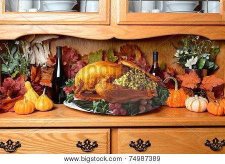 Thanksgiving turkey on a sideboard. The still life has fall leaves, pumpkins and decorative gourds wine bottles. The turkey is stuffed with garnish surrounding it on the platter.