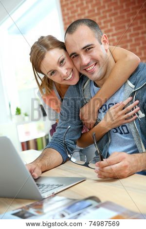 Cheerful couple websurfing on internet with laptop