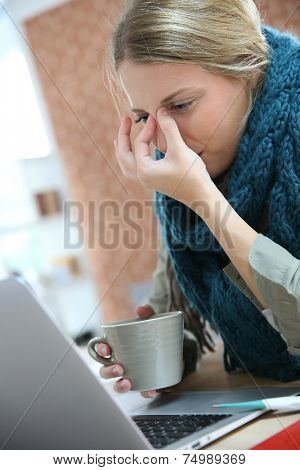 Young woman working at home and being sick
