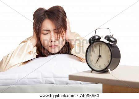 Asian Woman Covering Ears With Hands And Alarm Clock