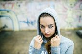 pic of graffiti  - Serious teenage girl with hood on listening to music from headphones standing on background of graffiti wall - JPG