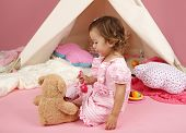 stock photo of teepee tent  - Happy toddler girl engaged in pretend play tea party with stuffed bear toy indoors at home with a teepee tent - JPG