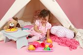 foto of teepee tent  - Happy toddler girl engaged in pretend play tea party indoors at home with a teepee tent - JPG