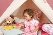 image of teepee tent  - Happy toddler girl engaged in pretend play tea party indoors at home with a teepee tent - JPG