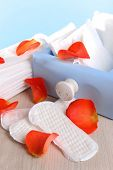 image of menses  - Sanitary pads in box and rose petals on wooden table on light blue background - JPG