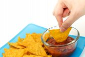 stock photo of dipping  - Dipping tortilla chips with salsa sauce in dish on isolated white background - JPG