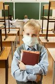 stock photo of epidemic  - School children in medical face mask are learning in the half empty classroom during epidemic of flu - JPG