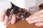 stock photo of sewing  - woman sews on the sewing machine macro - JPG